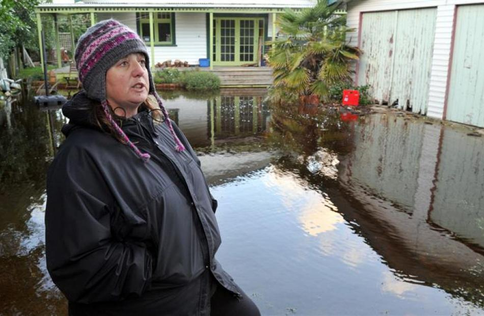 Aramoana League member Vicki Wilson stands next to one of about a dozen Aramoana properties which...