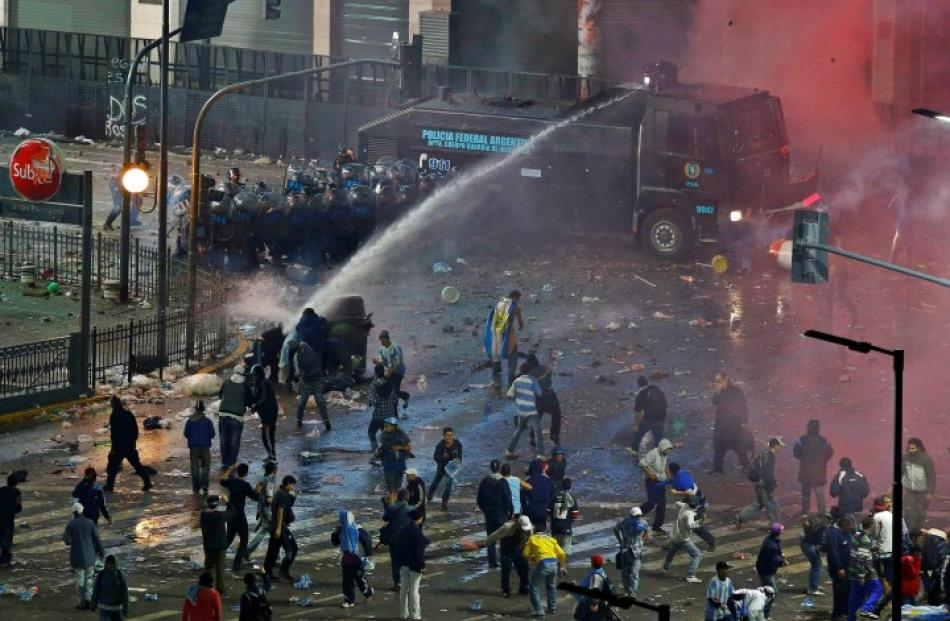 Argentina fans clash with riot police in a public square viewing area in Buenos Aires following...