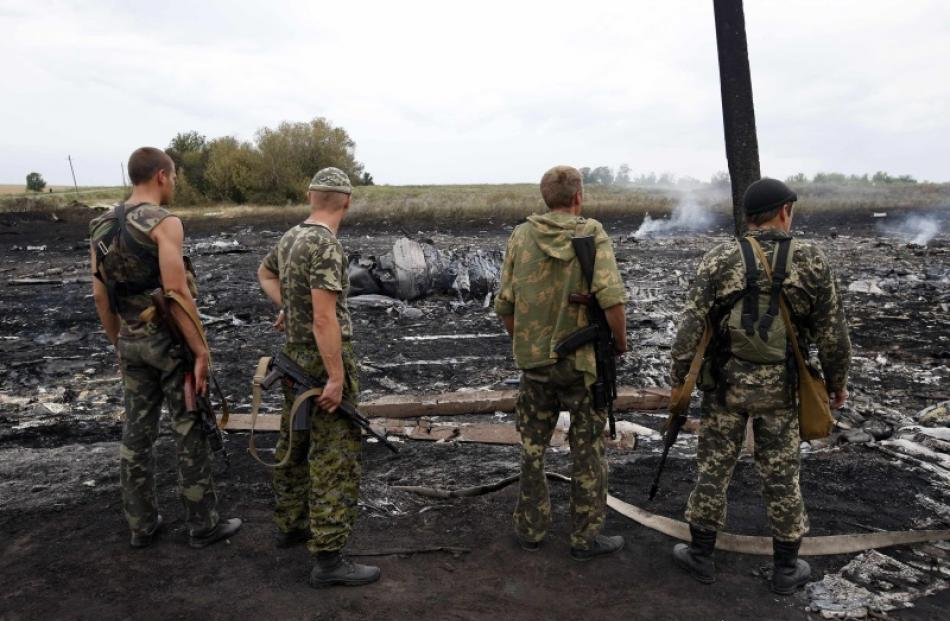 Armed pro-Russian separatists stand at the site of a Malaysia Airlines Boeing 777 plane crash...