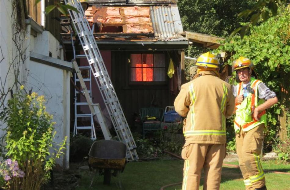 Arrowtown and Frankton firefighters on Easter Monday assess the damage resulting from  a fire in...