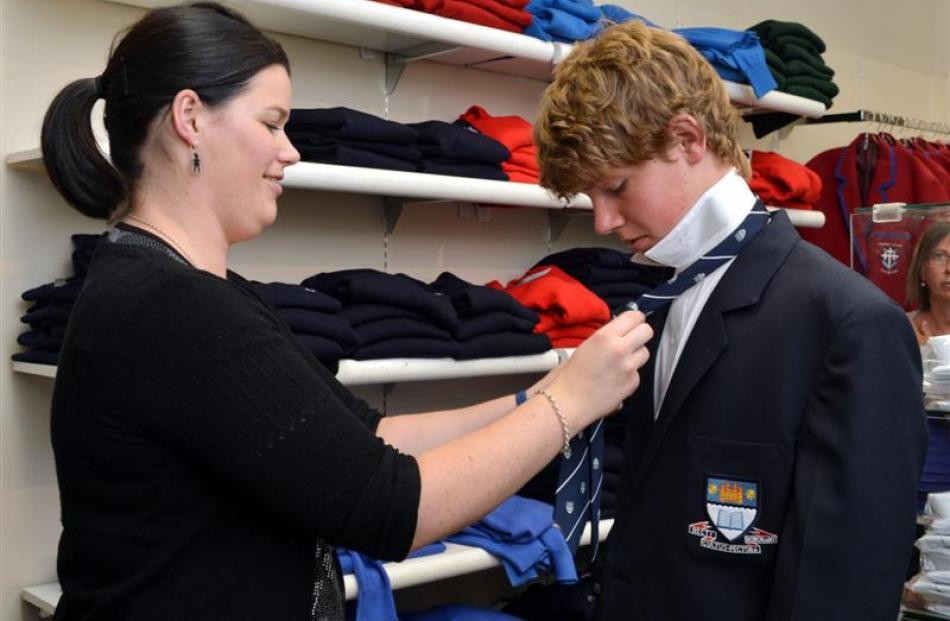 Arthur Barnett store assistant Hannah Joseph helps to fit Otago Boys' High School pupil Cameron...