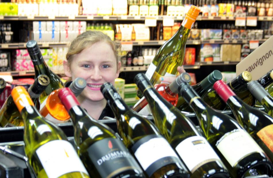 Assistant manager of Henry's Centre City Rebecca Glover restocks the wine shelves yesterday....