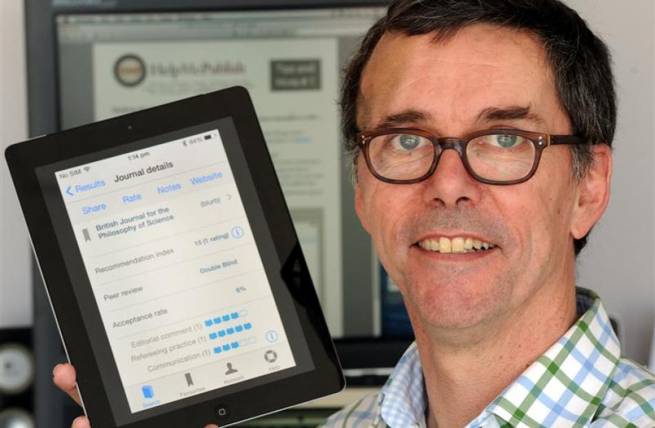 Associate Prof James Maclaurin with his ''HelpMePublish'' iPhone app. Photo by Craig Baxter.