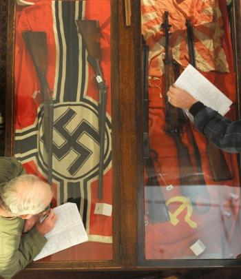 Auction goers make notes on a cabinet containing flags and shotguns during an antique,...