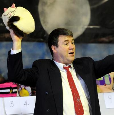 Auctioneer Jeremy Anderson collects bids on a sleeping cat tea cosy at Nga Maara Hall at Sacred...