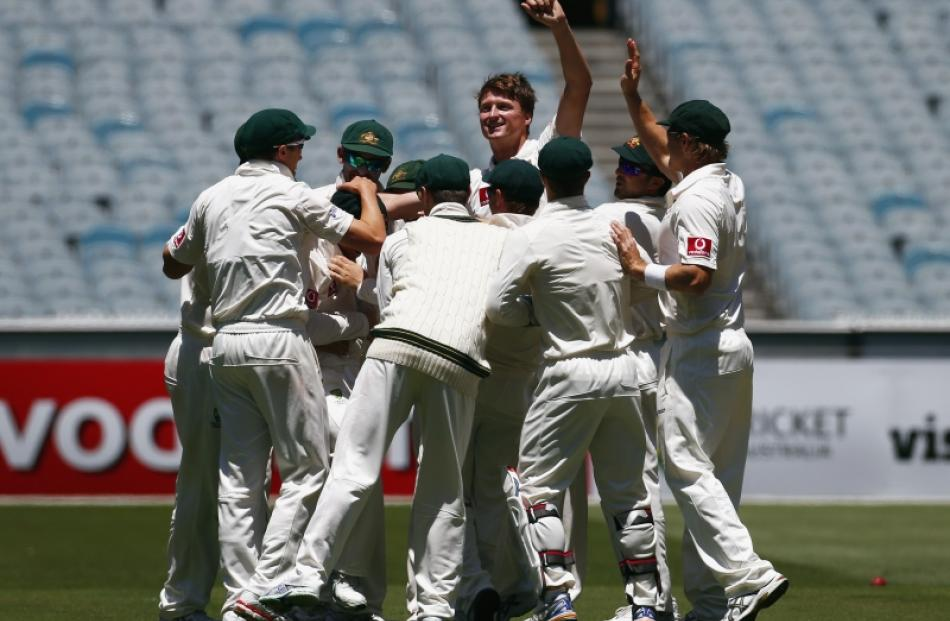 Australia's Jackson Bird (centre) celebrates with team mates after taking the wicket of Sri Lanka...
