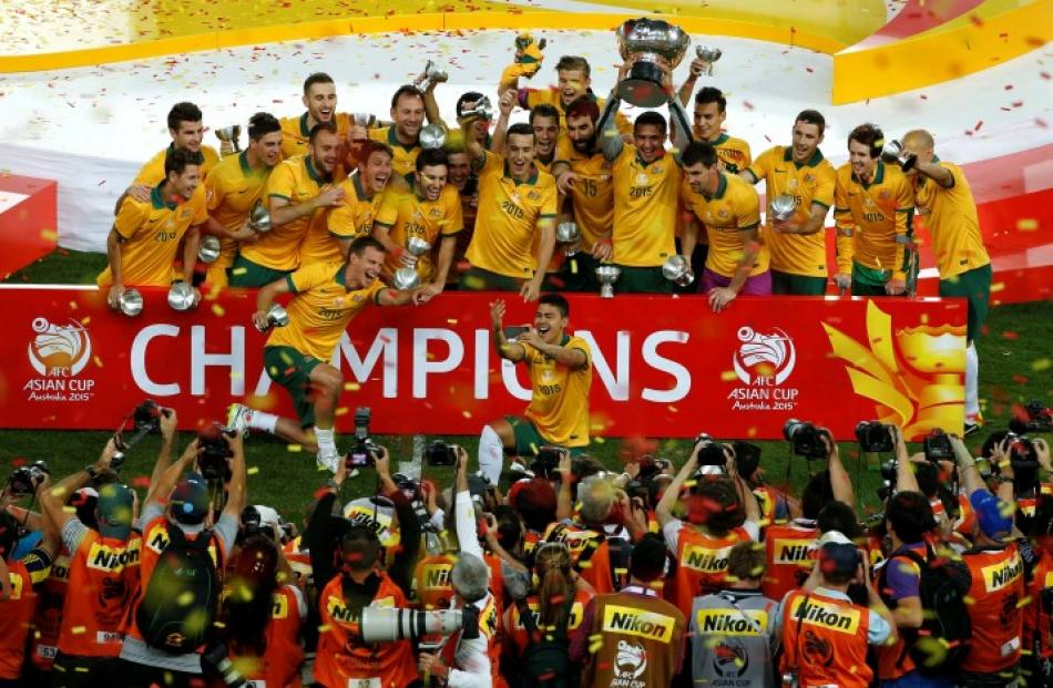 Australia s players celebrate with the Asian Cup trophy after winning the  final against South. 614bcdccc