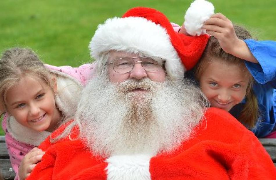 Australian tourists Natalia (8) and Anastasia (9) Chochol, of Brisbane, meet Santa (Graeme...