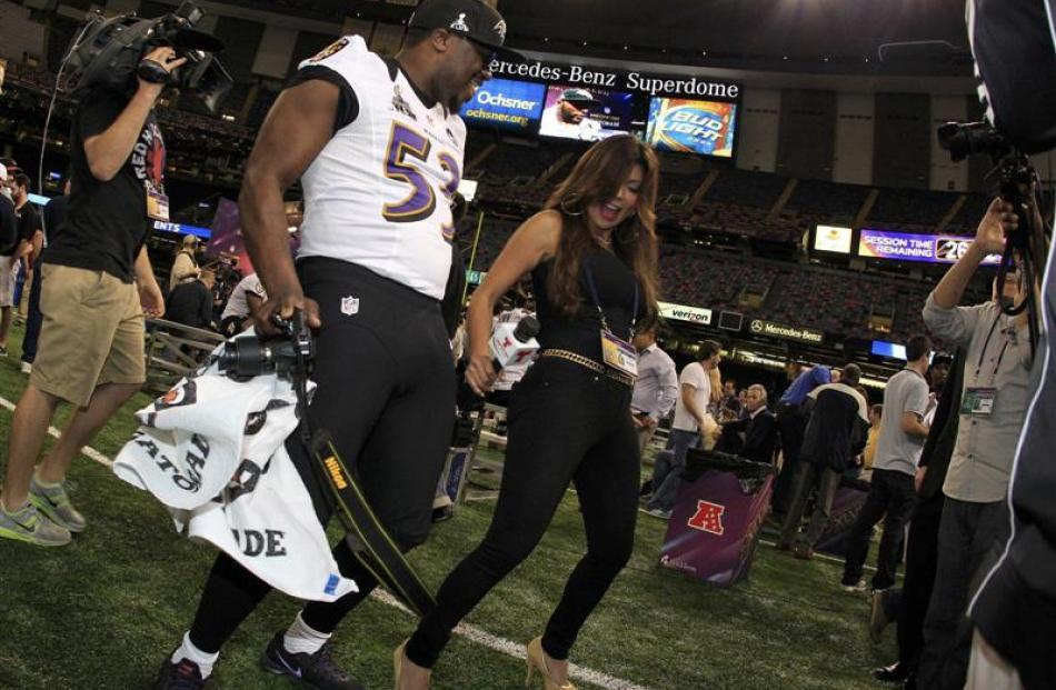 Baltimore Ravens' Jameel McClain (left) dances with Telemundo reporter Mirrella Grisales during...