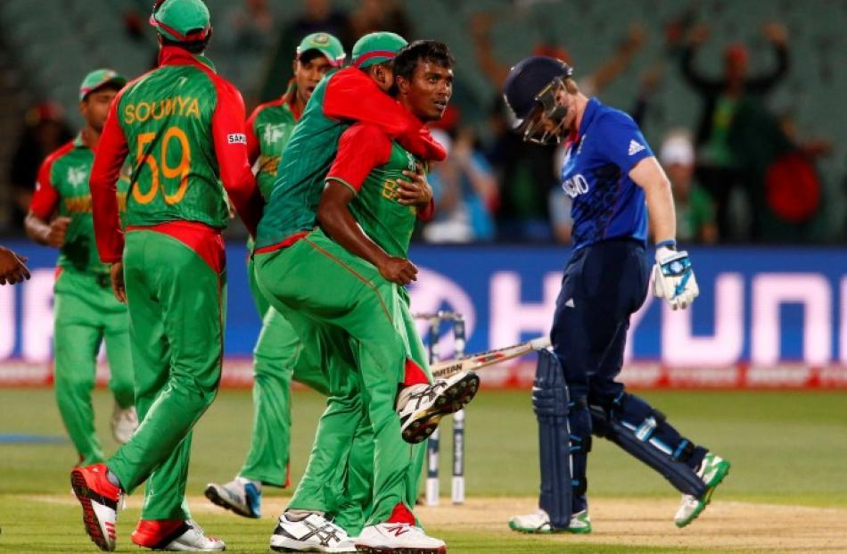 Bangladesh players celebrate the dismissal of England captain Eoin Morgan (R). REUTERS/David Gray