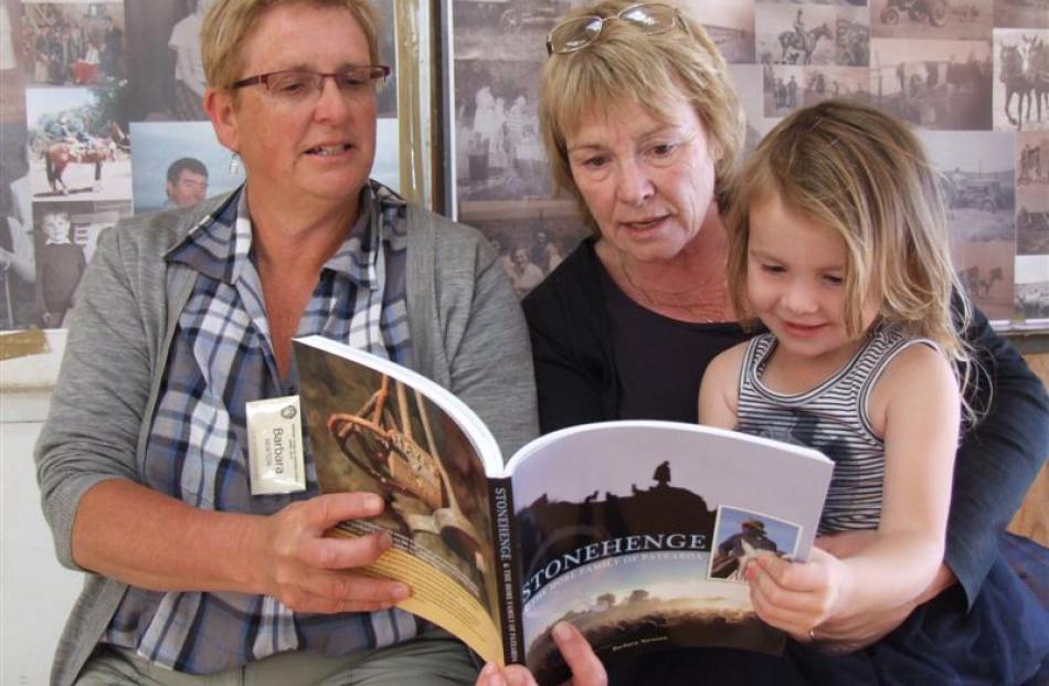 Barbara Newton (left), Sue Hore and Ruby Hore (3) look through Mrs Newton's book <i>Stonehenge...