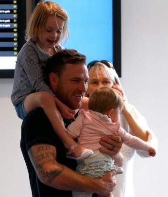 Black Caps captain Brendon McCullum holds his daughters after arriving at Auckland Airport today....