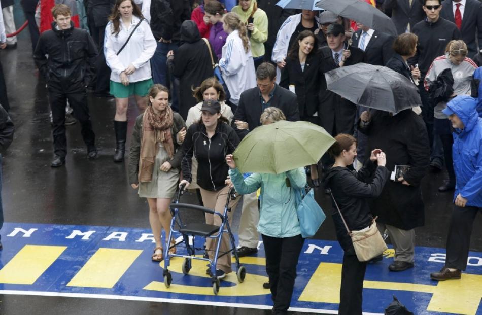 Boston Marathon bombing survivor Erika Brannock crosses the finish line following a ceremony on...
