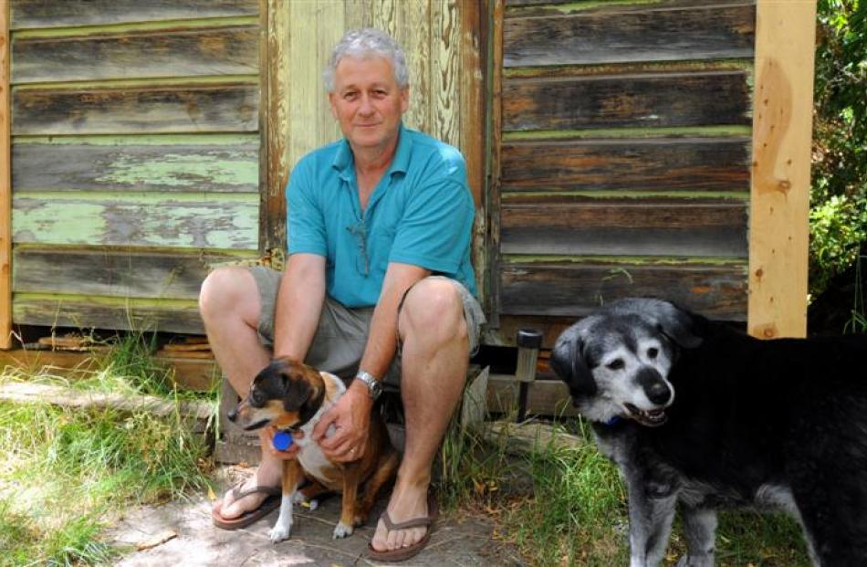 Bryan Young sits outside one of his two huts on his section in Patearoa with his dogs, Millie ...