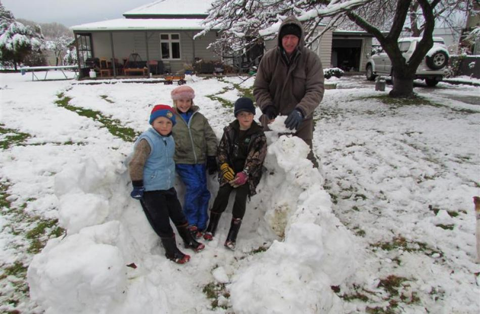 Building an igloo with the help of their father, Chris Horn, are (from left) Lochie (5), Holly (9...