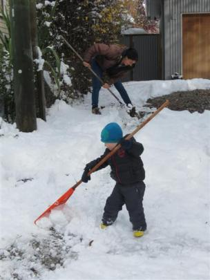 Carter Sanson (2) helps his mother, Ros, clear snow from their driveway in Arrowtown yesterday....