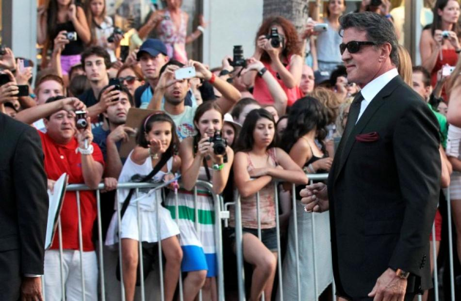 Cast member Sylvester Stallone (R) arrives at the premiere of 'The Expendables 2' at the Grauman...