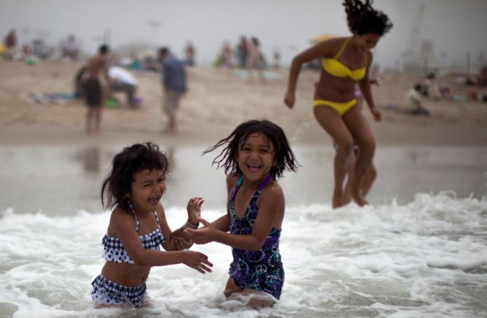 Celeste Hidalgo (7, R) and Alana Griego (5) cool off in the Pacific Ocean in Santa Monica,...