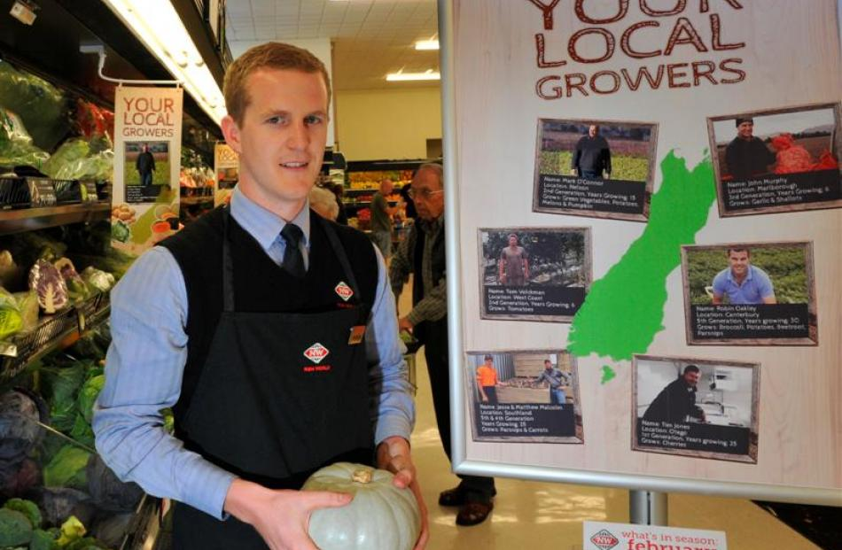 Centre City New World's Braedan Trompetter beside the local growers poster being displayed in...
