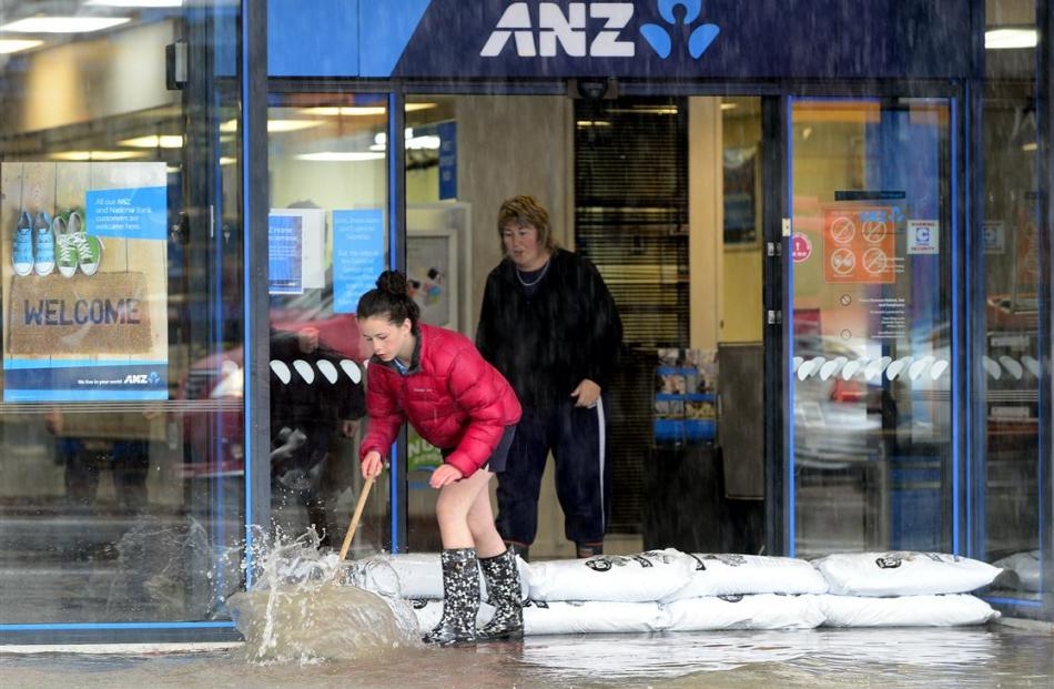 Charlotte Wilson (12) of Mosgiel,and Michelle Pennington  clear water from the ANZ Bank after a...