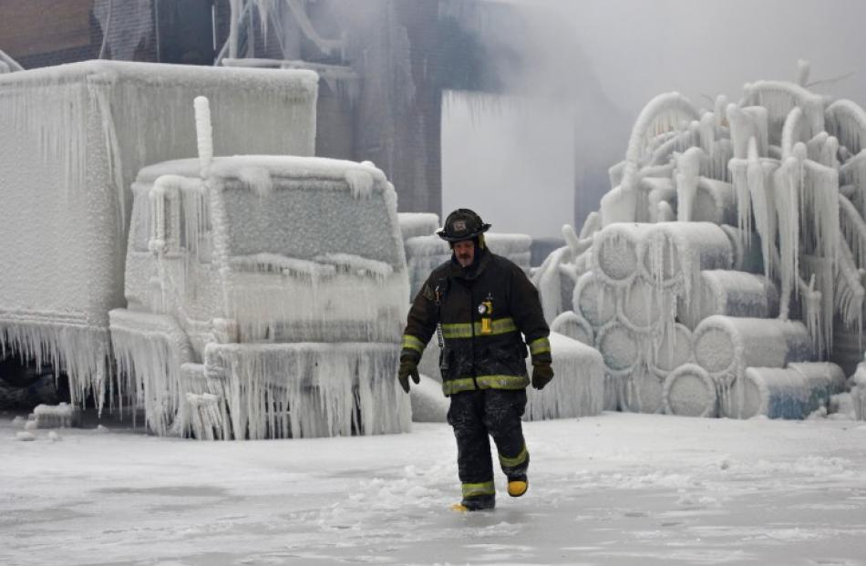 Chicago Fire Department Lieutenant Charley De Jesus walks around an ice-covered warehouse that...
