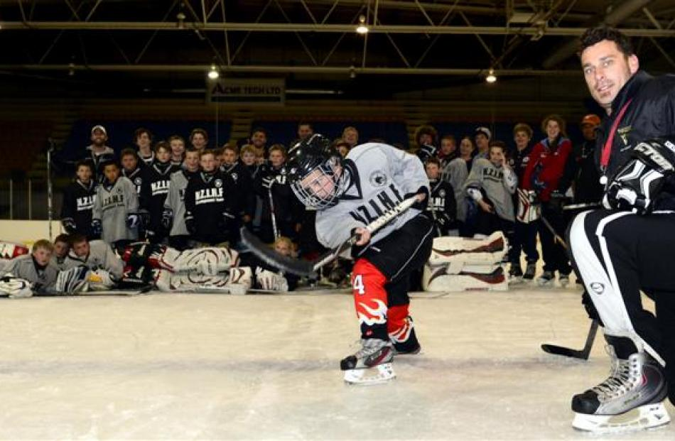 Christchurch ice hockey player Harry Louw (9) shows his shooting technique in front of coach...