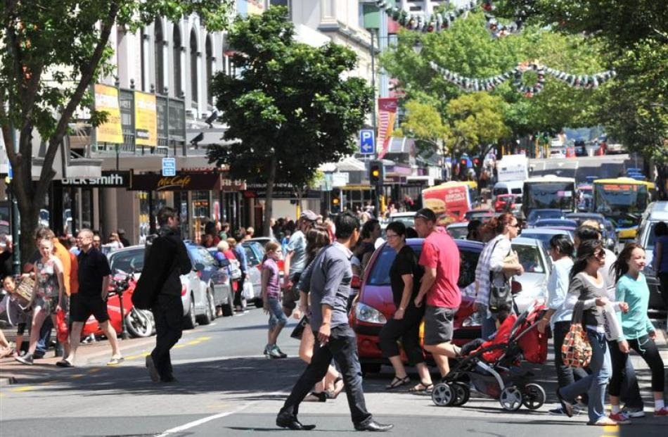 Christmas shoppers walk across a busy George St on Saturday afternoon.