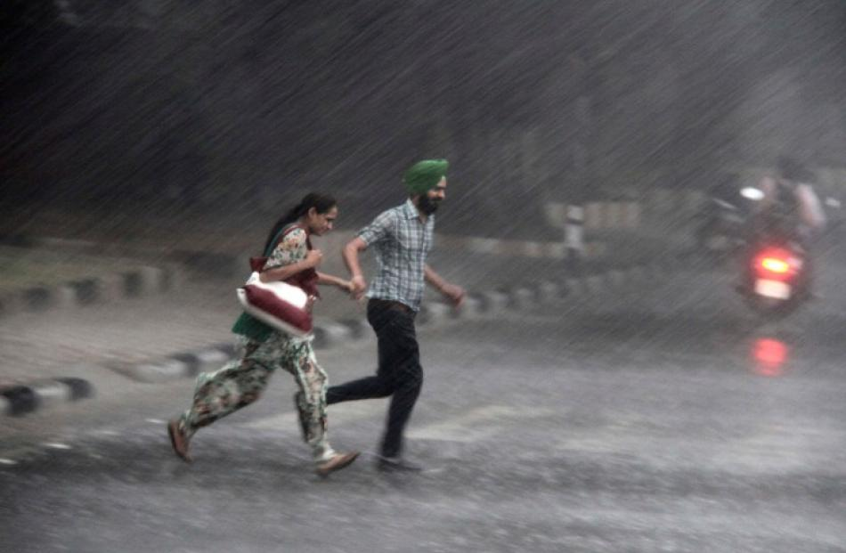 Commuters run for cover as they cross a road during monsoon rains in the northern Indian city of...