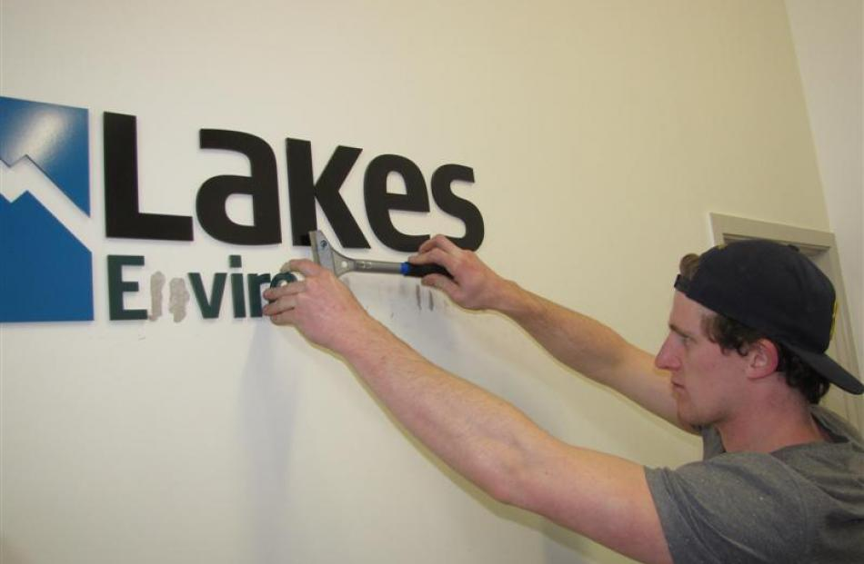 Connor Harrison, of Sign It Signs, removes Lakes Environmental signs from the authority's office...
