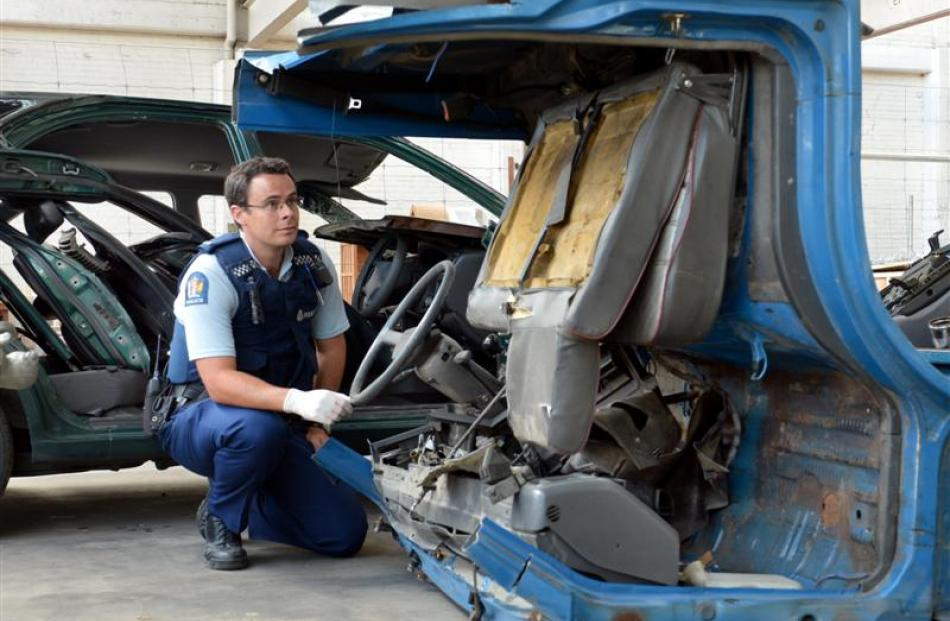Constable Anthony Bond inspects what remains of a flatbed Nissan Atlas truck, which was stolen...