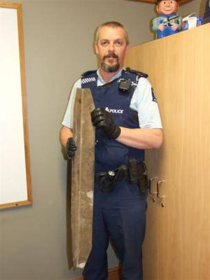 Constable Terry Erceg holds the piece of metal which came off a truck's trailer and hit a car on...