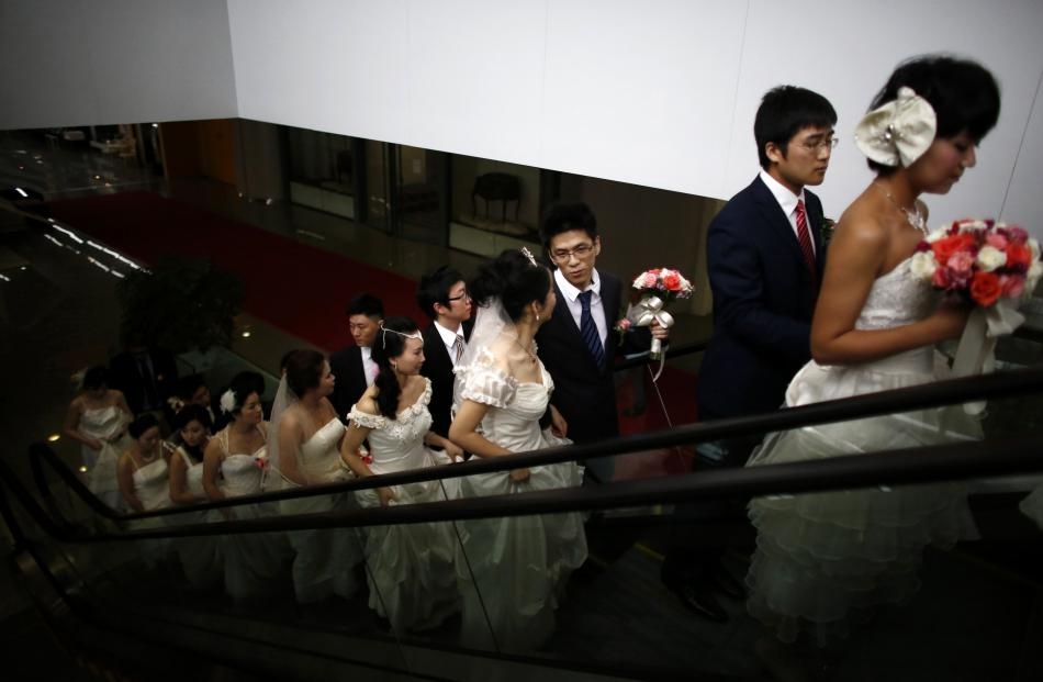 Couples take an escalator as they participate in a staged mass wedding, organised as part of a...