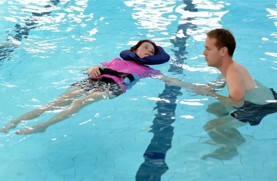 Courtney Donald swims in the physio pool with the help of physiotherapist Mark Shirley. Photo by...