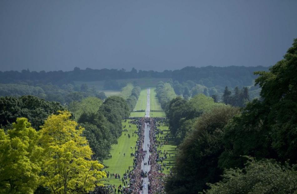 Crowds gather to watch as the Olympic Flame arrives at Windsor Castle, west of London yesterday....