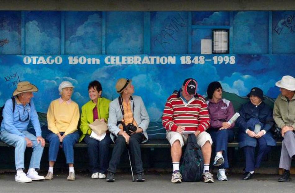 Cruise-ship passengers wait in a Cumberland St, Dunedin, bus stop for a ride back to Port...