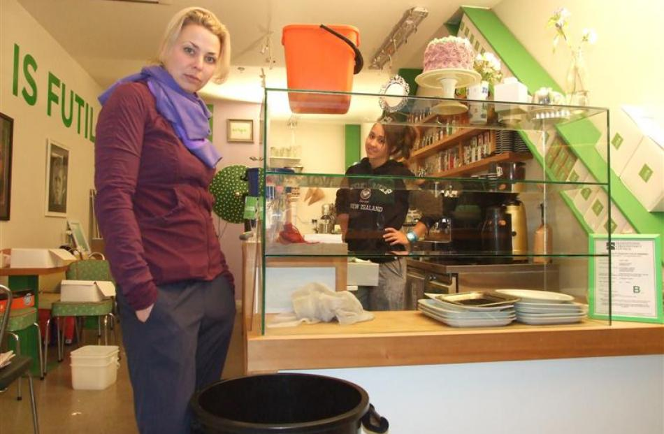 Cup and Cake's Jaimie Stodler (left) and Jamille Bezerra stand with the shop's empty cabinet...