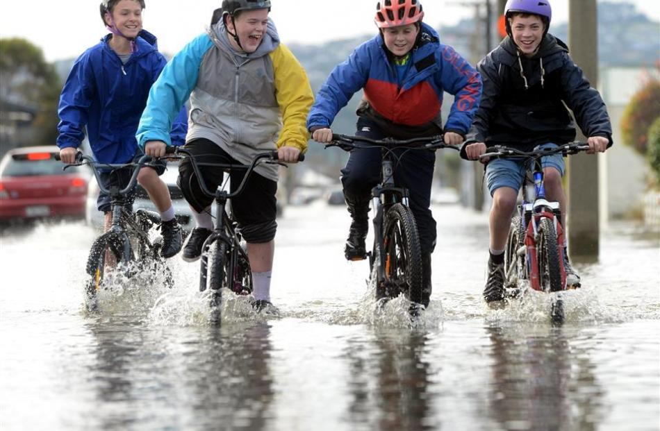 Cycling in a flooded Bay View Rd, South Dunedin, after the June floods are (from left) Jevon...