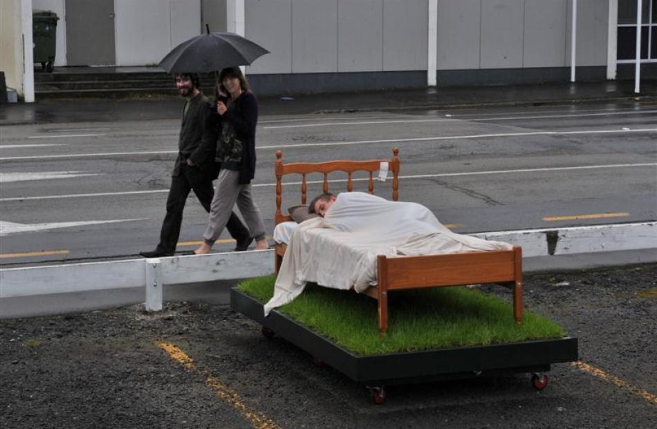 Daniel Benson-Guiu and Ashlea Muston (top) walk past art student Clarke Hegan as he sleeps in a...