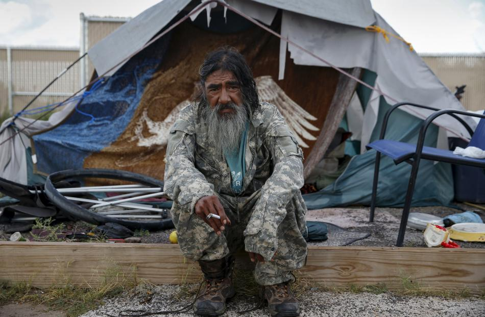 Daniel J. Wabsey, a 58-year-old war veteran, sits outside his tent at Camp Hope in Las Cruces,...