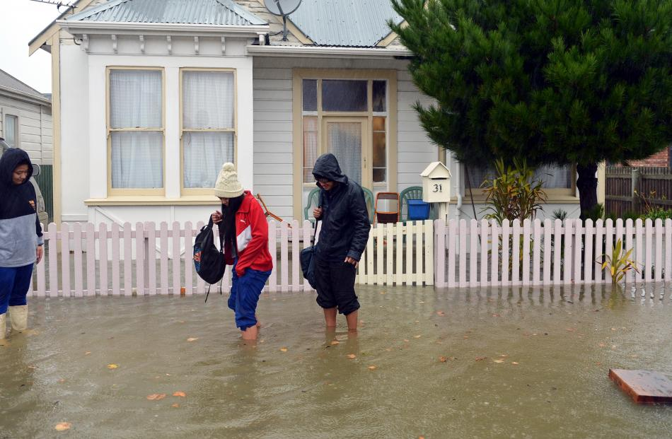 Darcel, Chantelle and Felix Pese evacuate their Nicholson St house about noon as floodwaters rise...