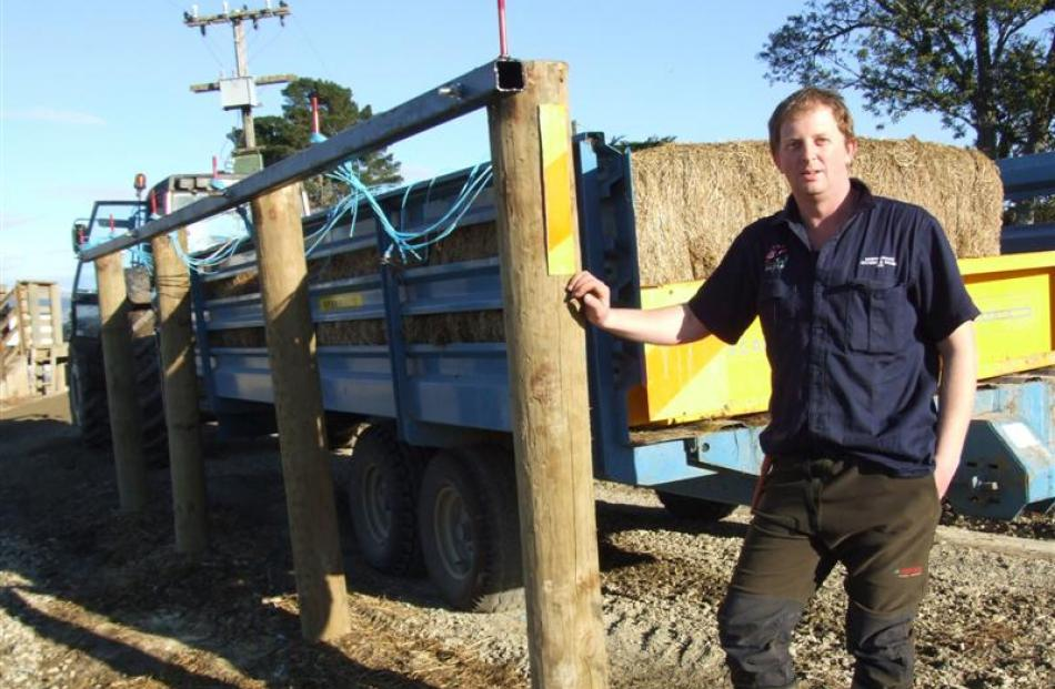 Dave McCabe with the system he has designed to easily pull strings from bales on feed-out wagons....