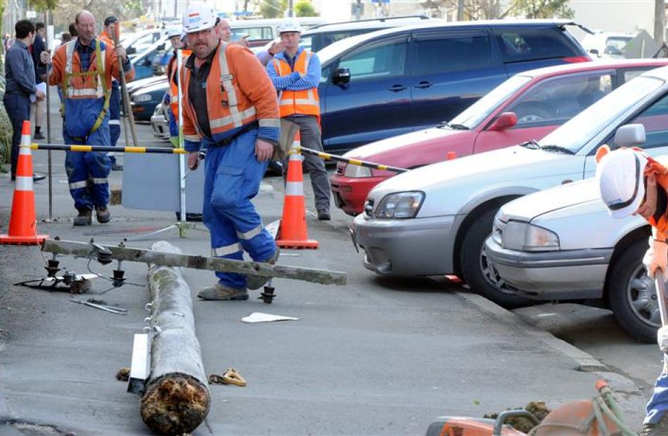 Delta workers deal with a power pole, felled by wind, that struck  a car in Castle St, Dunedin,...