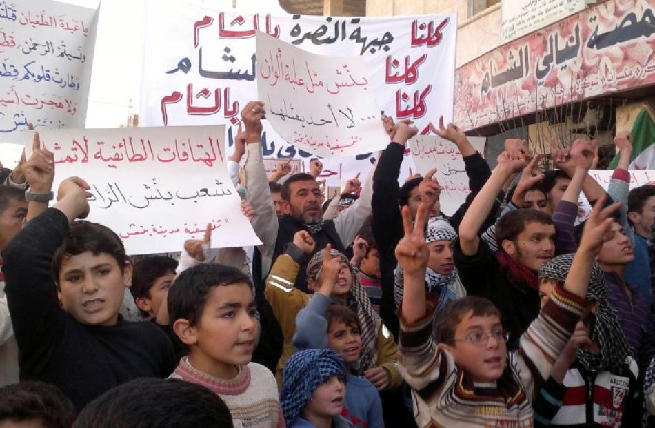 Demonstrators hold banners during a protest against Syria's President Bashar al-Assad in Binsh,...
