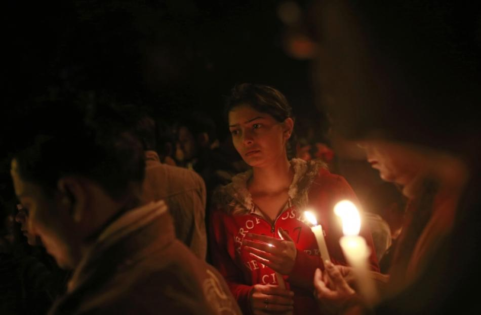 Demonstrators hold candles during a candlelight vigil for a gang rape victim who was assaulted in...