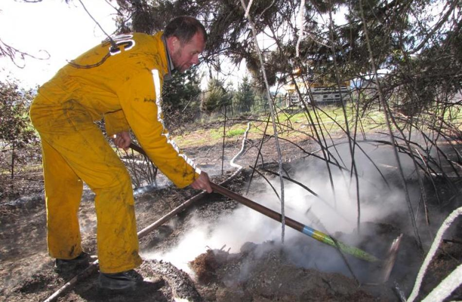 Department of Conservation rural firefighter Mark Mawhinney, of Queenstown, rakes over smoky...