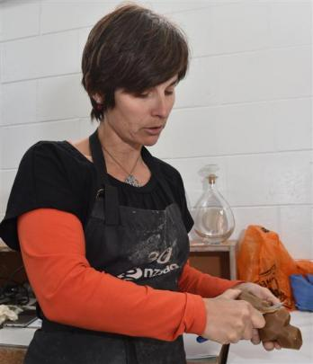 Di Tocker works on a wax model that will form the  shape of one of her cast-glass works. Photos...