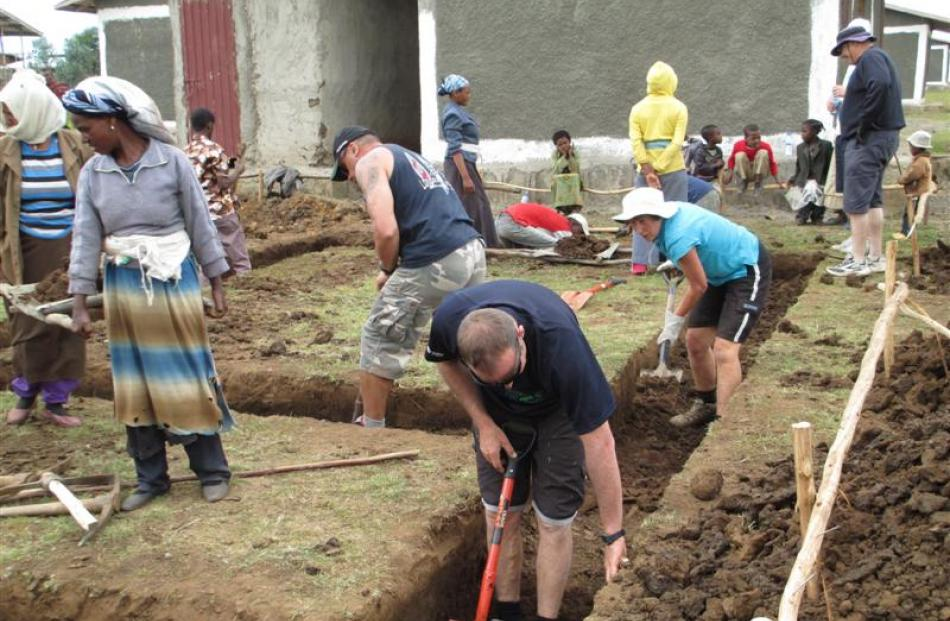 Digging foundations for a two-room home are Steve  Calley (front right), Guy  Kingi (left), Rose...