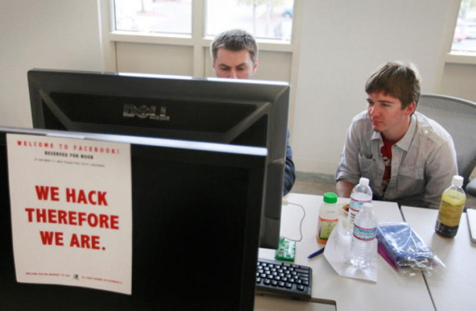 Dimitry Soshnikov (left) writes code as Ryan Patterson helps him during a boot camp at Facebook's...