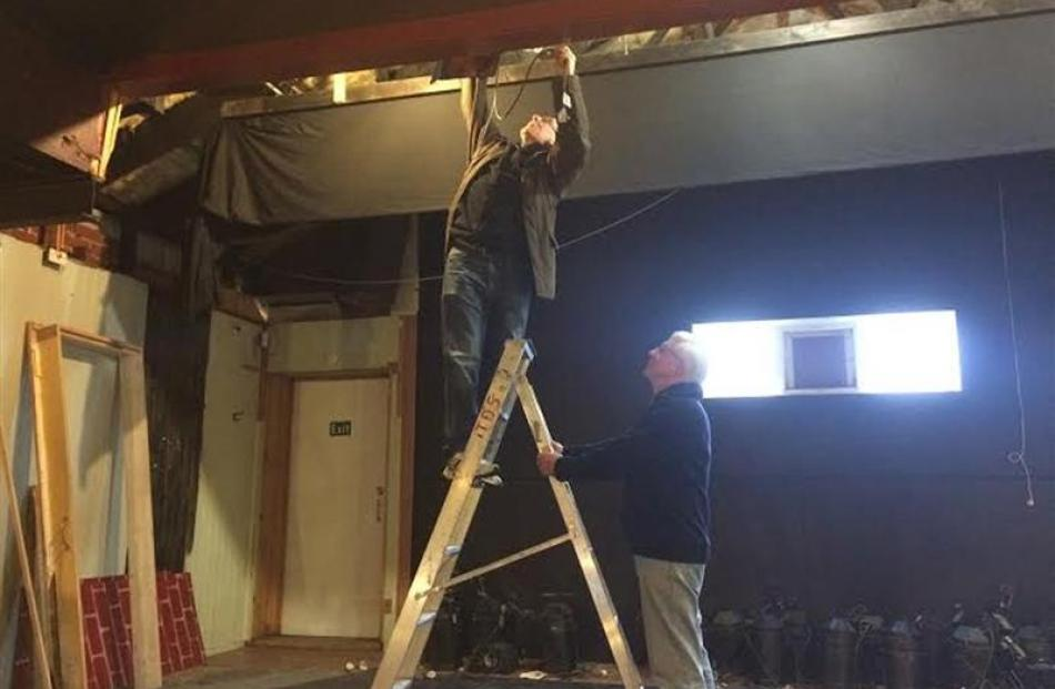 Doug Leggett holds a ladder for Keith Richardson, who is removing lights. Photo by Thomas Dunn.