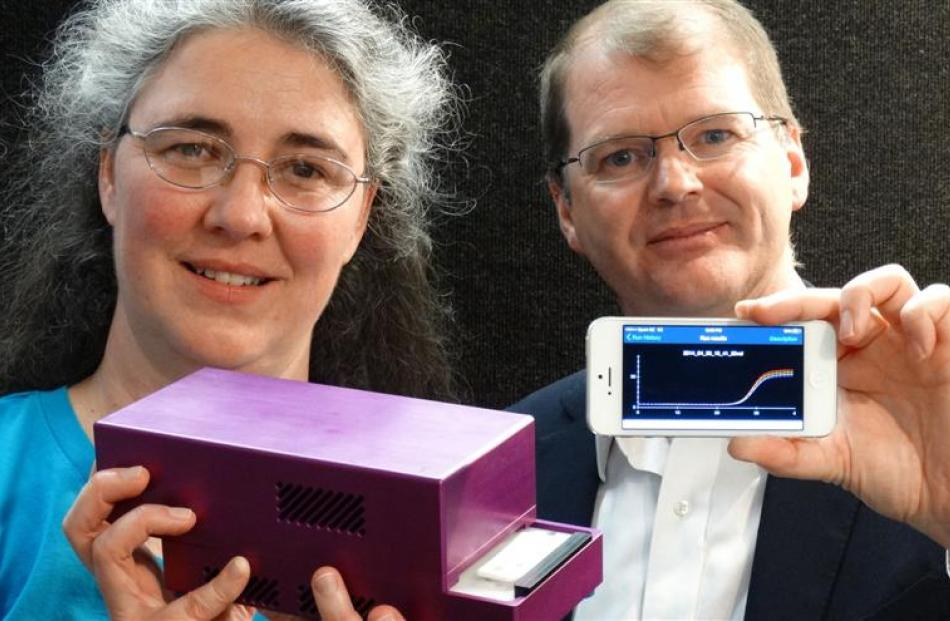 Dr Jo-Ann Stanton and Paul Pickering with a handheld DNA diagnostic unit, connected to a...